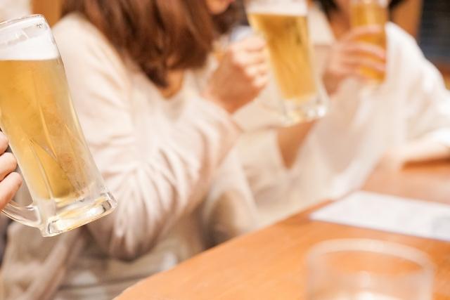 飲み会で女性がビールを飲んでいる様子