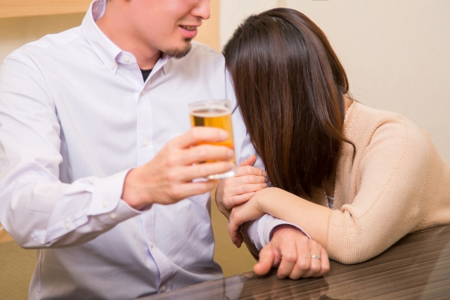 飲み会で女性が男性に身体をもたれかけている様子