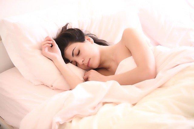 ベッドで寝る美人女性