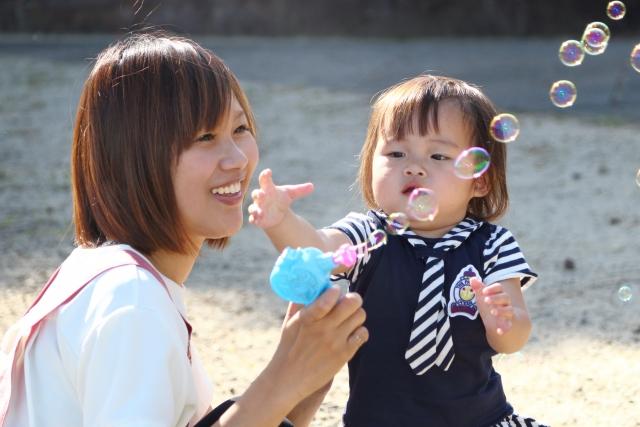 子供と遊んでいる保育士