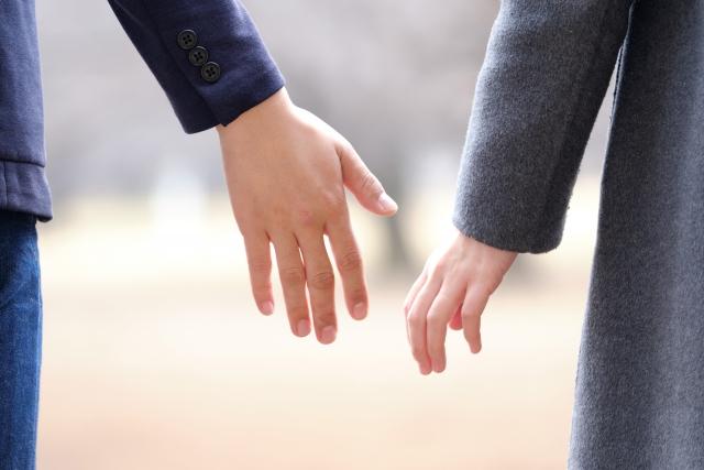 手を繋ごうとする男女