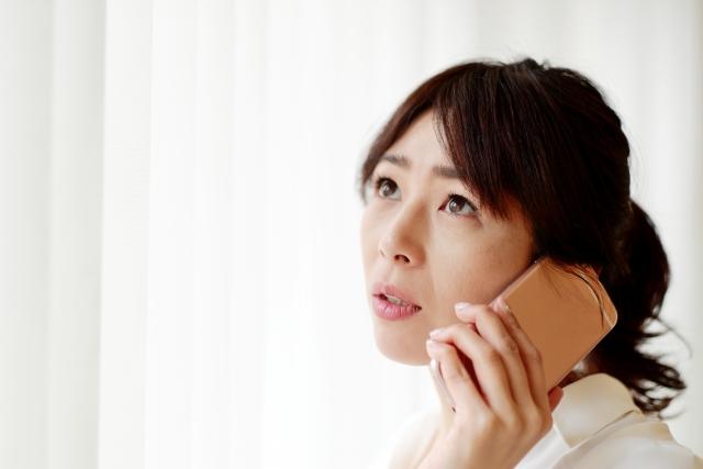 心配しながら電話している女性