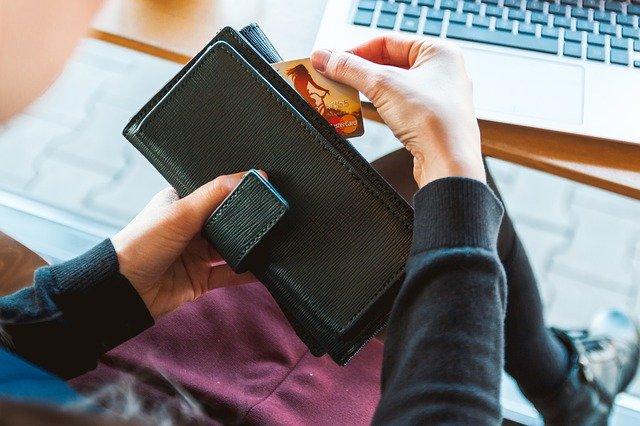 財布からカードを出す男性