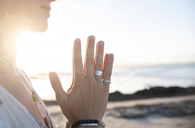 海辺で手を合わせる女性