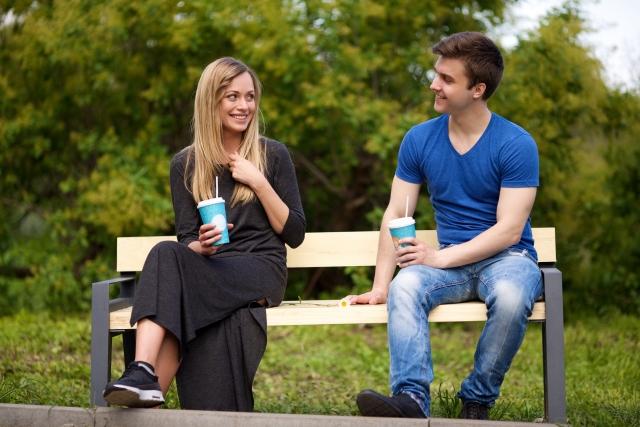 ベンチに座ってドリンクを飲むカップル
