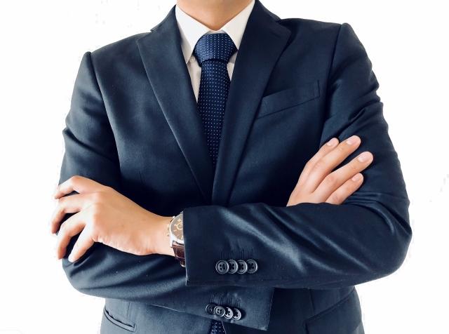 腕を組むスーツの男性