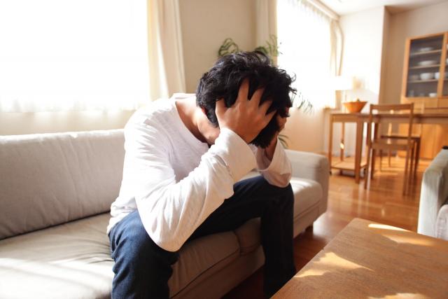 ソファで頭を抱える男性